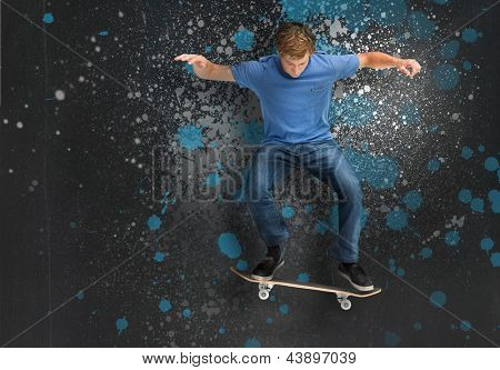 Cool young skateboarder doing an ollie trick on blue and grey paint splattered background