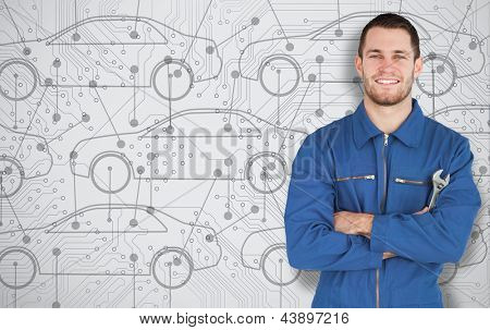 Young smiling mechanic standing in front of cars background