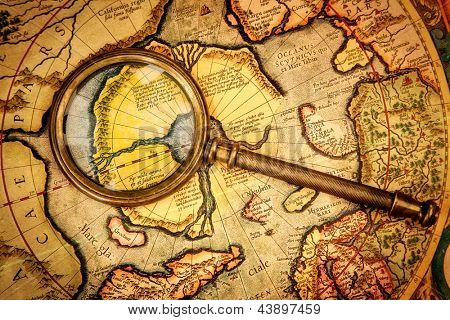 Vintage magnifying glass lies on the ancient map of the North Pole (also Hyperborea). Arctic continent on the Gerardus Mercator map of 1595.