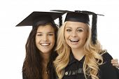 Closeup portrait of beautiful young females in graduation cap smiling happy, hugging.