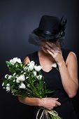 sad widow crying at husband's funeral