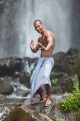 stock photo of qigong  - Young handsome man enjoying waterfall in the tropics - JPG