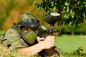 stock photo of paintball  - paintball player in protective uniform and mask aiming and shooting with paint marker gun outdoors - JPG