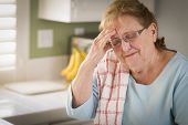 stock photo of grieving  - Sad Crying Senior Adult Woman At Kitchen Sink in Home - JPG