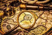 Vintage magnifying glass, compass, telescope lies on the ancient map of the North Pole (also Hyperbo