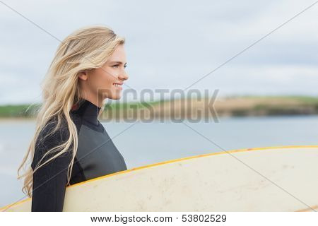 Side view of a beautiful young woman in wet suit holding surfboard at the beach