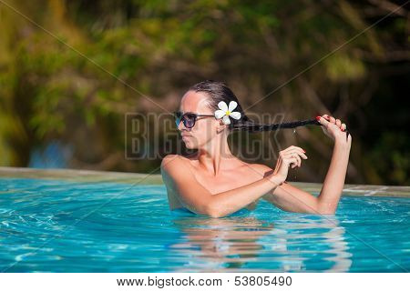 Portrait Of Young Beautiful Woman Enjoying The Luxury Quiet Swimmingpool