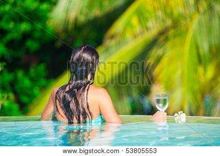 Back View Of Young Beautiful Woman Enjoying The Luxury Quiet Swimmingpool