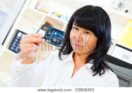 woman worker checks the printed circuit board microcontroller