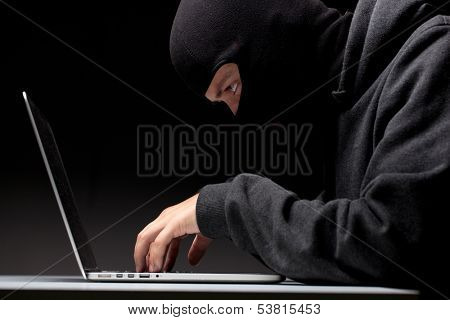 Computer hacker in a balaclava working in the darkness stealing data and personal identity information off a laptop computer