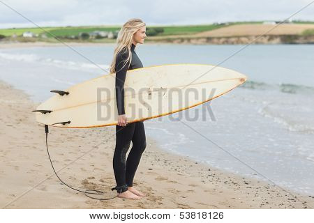 Full length side view of a beautiful young woman in wet suit holding surfboard at the beach
