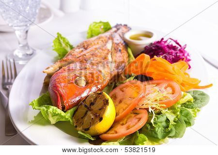 Full Cooked Tilapia Served With Vegetables And Fish Sauce Complimented With Ice Water