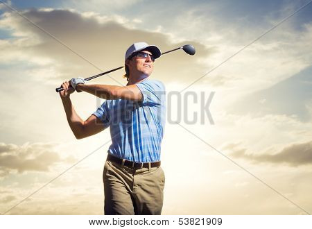 Golfer at sunset, Man swinging golf club with dramatic sunset sky backdrop
