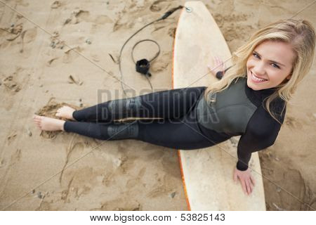 Overhead portrait of a smiling beautiful blond in wet suit with surfboard at the beach