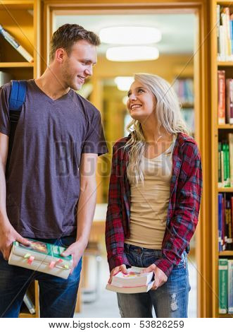 Smiling young couple holding books as they look at each other in the library