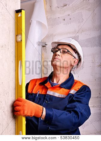 Mature man in builder uniform indoor.