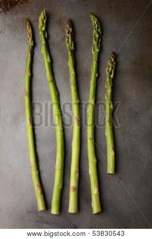 Five Asparagus Spears on a metal cooking sheet. Vertical format.