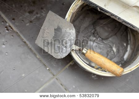 Dirty Trowel And Bucket On Building Site. Renovation At Home