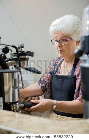 Senior barista preparing bayonet in espresso bar