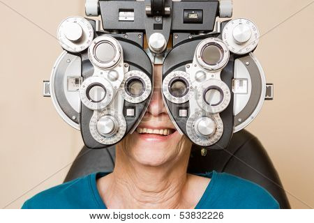 Happy senior woman looking through phoropter during eye exam