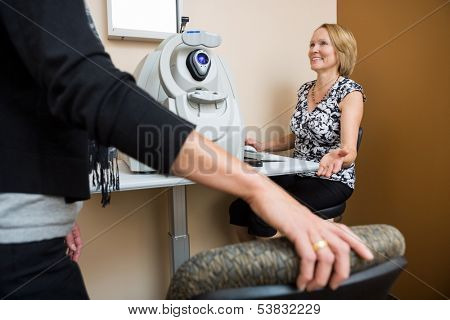 Happy mature female optician asking patient to sit in store
