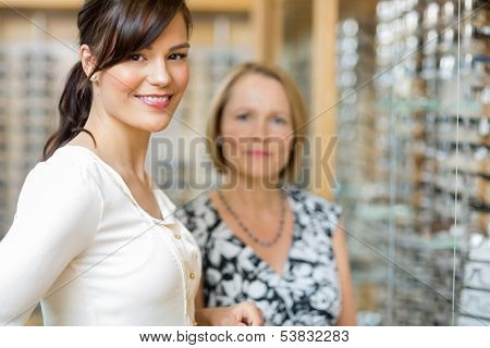 Portrait of beautiful salesgirl with senior woman in optician store