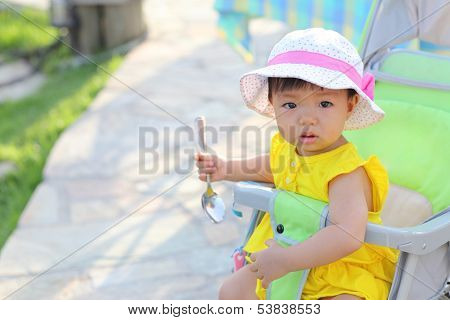 Little Girl Holding A Spoon And Sitting In Her Go-cart