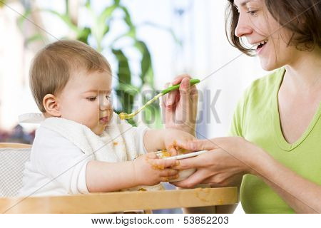 Sweet messy baby boy playing with food while his mother is feeding him with vegetable mash.