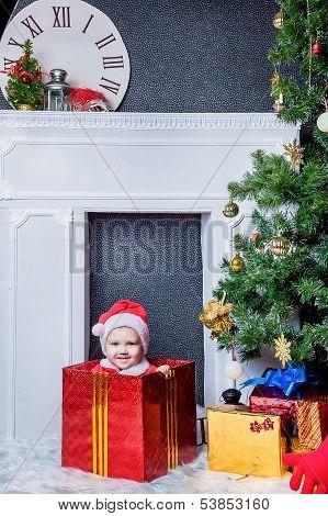 Boy dressed as Santa sitting in a gift box