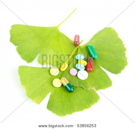 Ginkgo biloba leaves and pills isolated on white