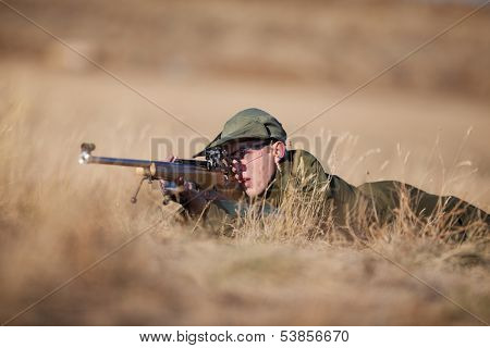 A young cadet laying in the dry grass target shooting.