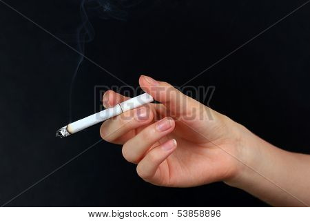 Woman hand holding cigarette with smoke, isolated on black