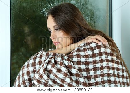 Lonely sad woman sitting on window