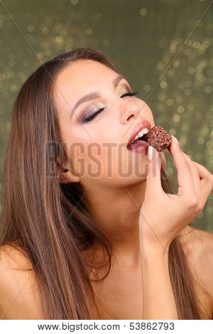 Portrait of beautiful young girl with chocolate candy on shiny background