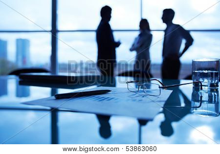 Close-up of business document, pen, glass of water and eyeglasses at workplace on background of office workers interacting