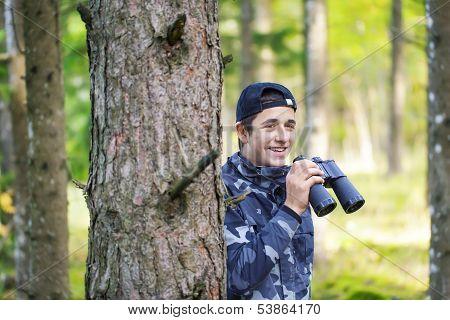 Teenager with binoculars in the woods