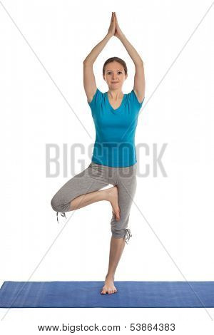 Yoga - young beautiful woman yoga instructor doing Tree pose asana (Vrikshasana) exercise isolated on white background