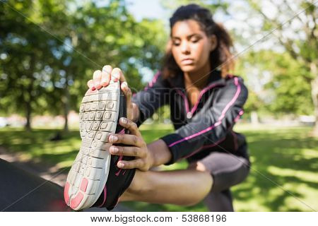 Pretty sporty woman stretching her leg while standing in the park
