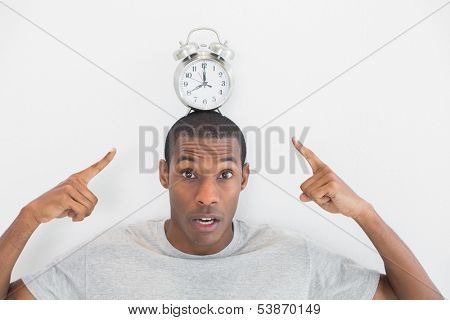 Close up portrait of a man pointing at alarm clock over his head against white background