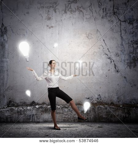 Image of businesswoman juggling with electrical bulbs