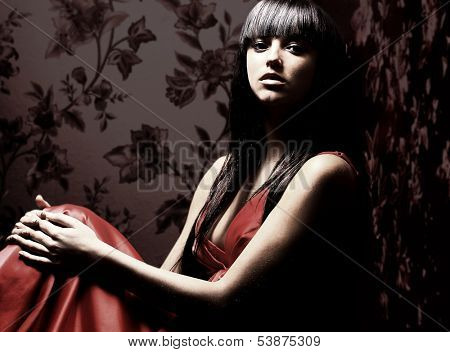 Beautiful woman seated in dark room