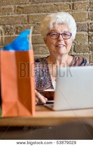 Portrait of senior woman with laptop sitting in coffeeshop