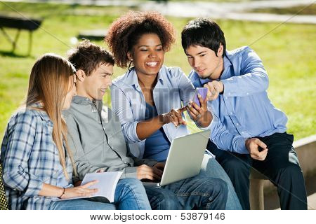 Happy young students with using mobilephone in university campus