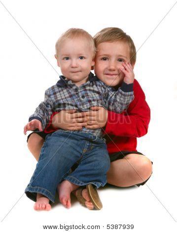 Dois irmãos sorrindo e sentar-se juntos em branco