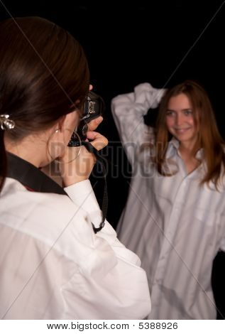 Girl Is Photographing A Model Against Black Background.