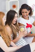 image of slumber party  - Cheerful young women surprising friend with a gift on sofa at home - JPG