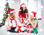 christmas, x-mas, winter, happiness concept - three smiling women in santa helper hats with many gif