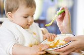 stock photo of messy  - Close up of lovely messy baby boy playing with food in the bowl while eating - JPG