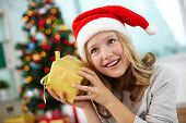 picture of guess  - Portrait of happy girl holding giftbox and guessing what is inside on Christmas evening - JPG
