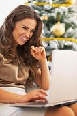 Portrait Of Happy Young Woman Using Laptop In Front Of Christmas